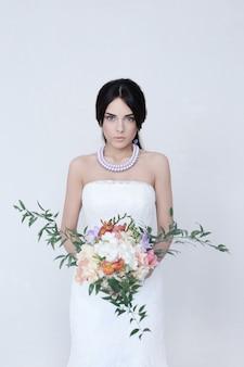 花の花束を保持しているウェディングドレスの美しい花嫁の女性