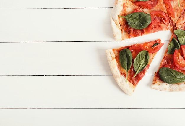 トマトのスライスとバジルの葉の伝統的なピザ
