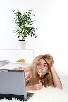 Женщина лежит на кровати и работает с ноутбуком