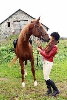 茶色の馬を持つ女性乗馬