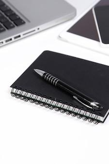 ラップトップ、スマートフォン、タブレット、メモ帳、テーブル上のペン