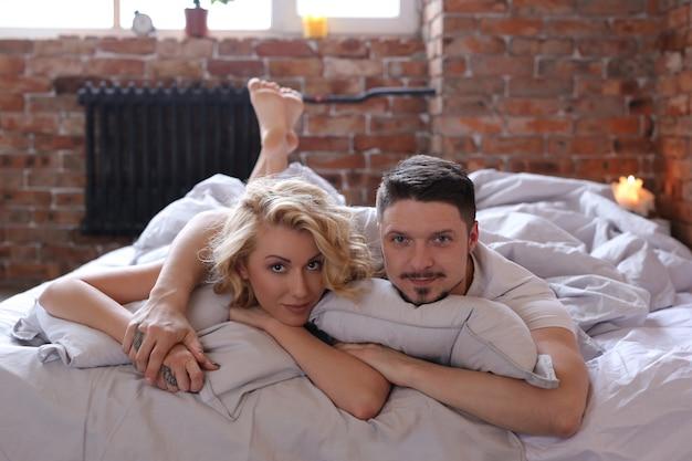ベッドで楽しんでいるカップル