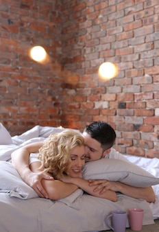 カップルはベッドに横になっていると愛を作る
