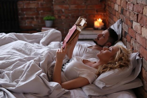 Пара читает книгу и спит в постели