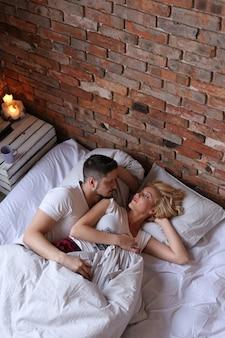 カップルを抱き締めると、ベッドで寝ています。