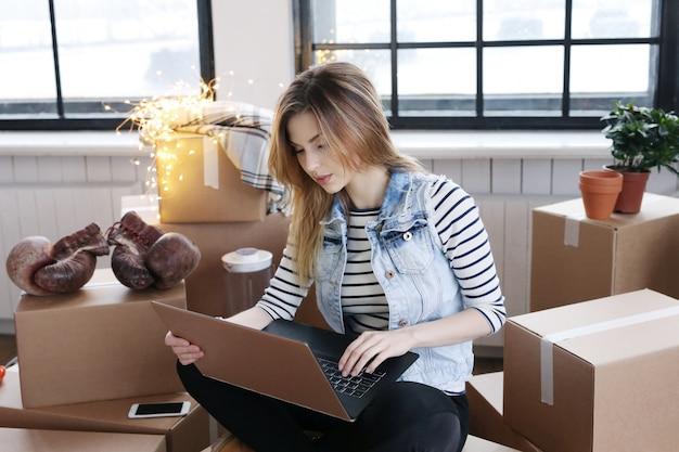 女性は貨物パッケージを使い終え、コンピュータを介して出荷するために宅配便業者に電話している