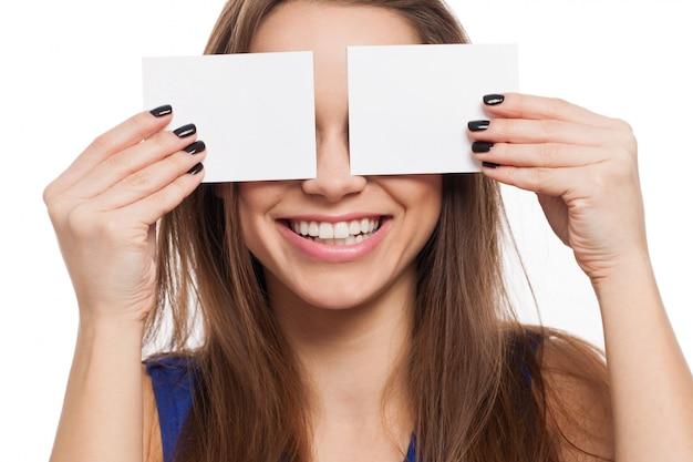 美しい若い女性はカードで目を閉じる