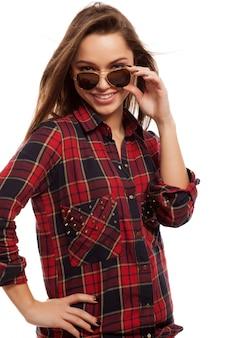 Молодая привлекательная женщина в рубашке и солнечных очках