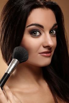 化粧ブラシと美しいブルネット