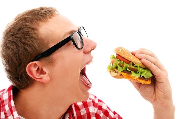 白で隔離されるハンバーガーを食べてメガネで変な男