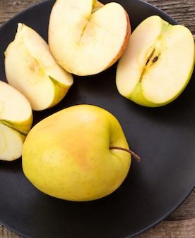 木製のテーブルの上の皿においしいリンゴ