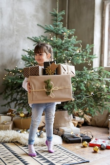 Девочка держит рождественские подарочные коробки