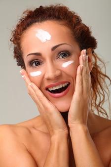 顔にクリームを持つ美しい女性