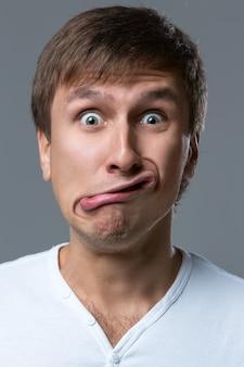 Большеголовый парень делает сумасшедшие эмоции