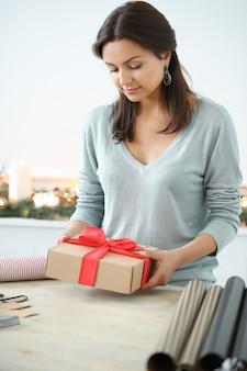Молодая женщина, упаковка рождественские подарки