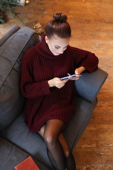 Женщина на диване с планшетом