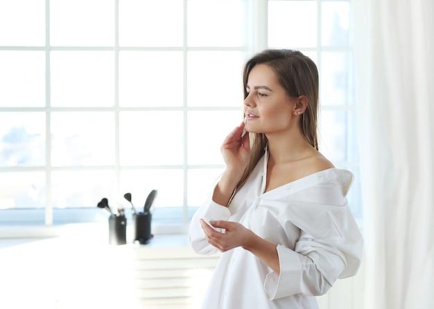 若い女性は、メイク落としワイプで顔のメイクを削除します。