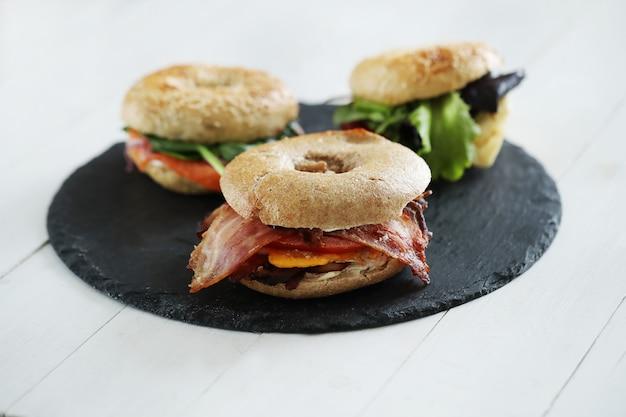 Вкусный бутерброд с бубликом и беконом