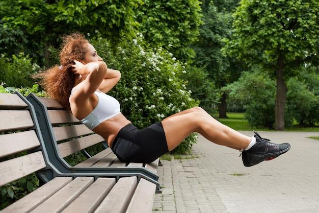 フィットネス女の子は公園でエクササイズ
