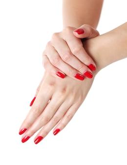 赤いマニキュアと女性の手