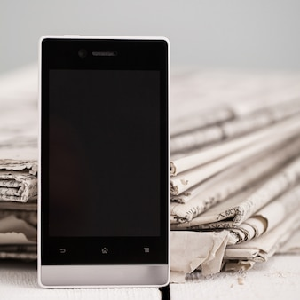 スマートフォンを搭載した新聞の山