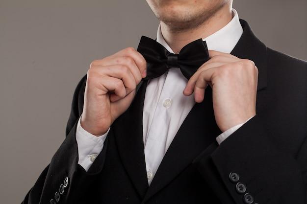 男の手が蝶ネクタイに触れる