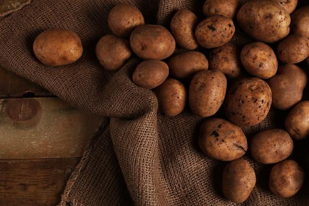 机の上の素朴な皮が付いていないジャガイモ