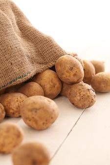 テーブルの上の素朴な皮が付いたままのジャガイモ