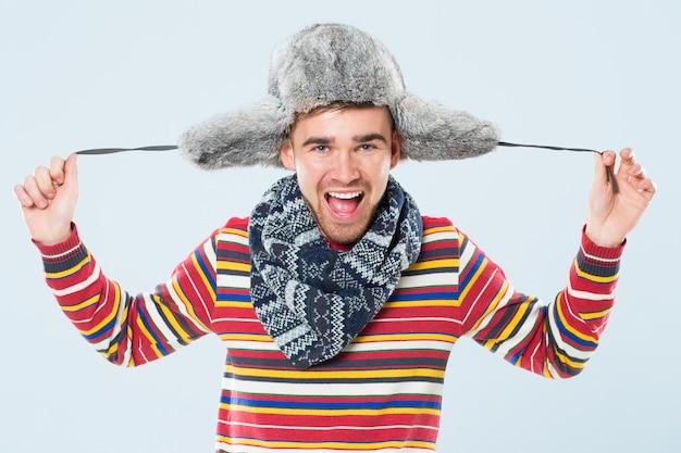 毛皮の帽子を持つハンサムな男