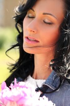 花束と公園で美しい女性