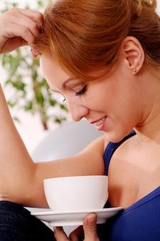 中年の幸せな女性は彼女のお茶を楽しむ