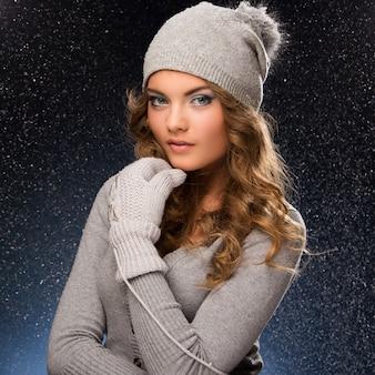 Симпатичная кудрявая девушка носить варежки во время снегопада
