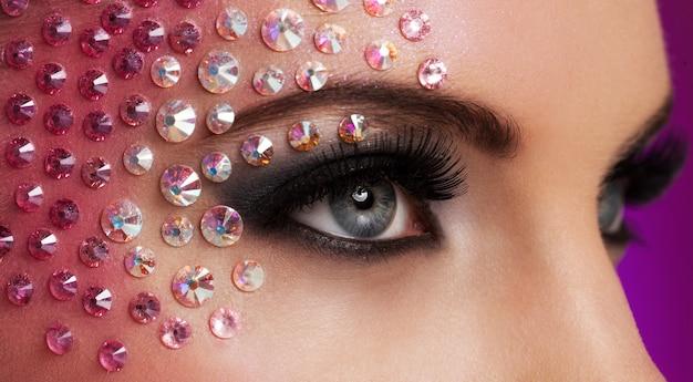Крупным планом изображение глаз с алмазной косметикой