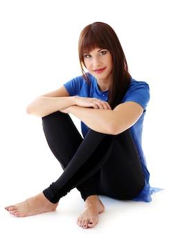 Женщина в леггинсах сидит на полу