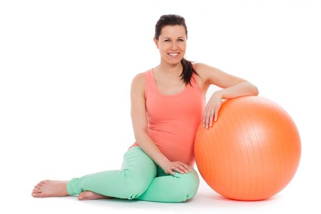 Красивая беременная женщина с мячом