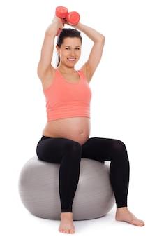 Беременная женщина работает с гантелями