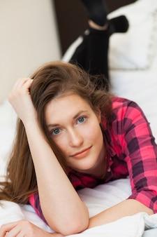 Симпатичная молодая девушка отдыхает на кровати