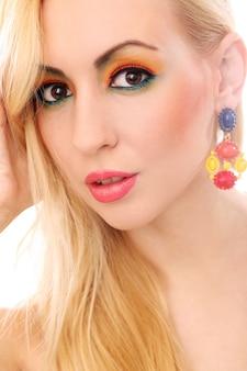彼女のかわいい色の外観を示す金髪の女性