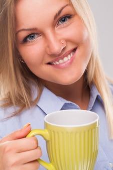 マグカップを持つ若いブロンドの女性
