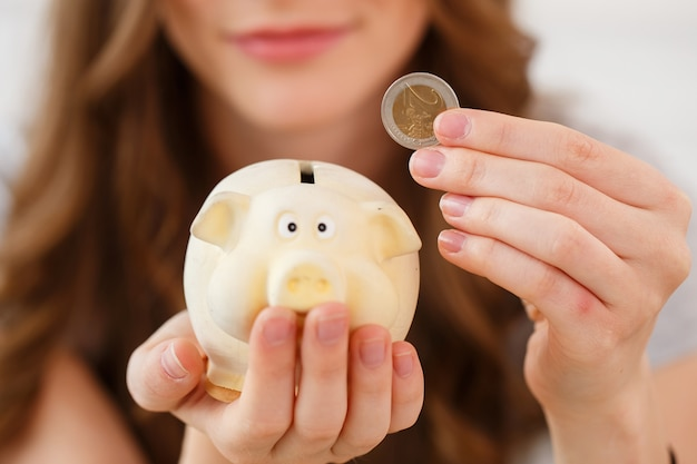 お金、金融。貯金箱を持つ女性