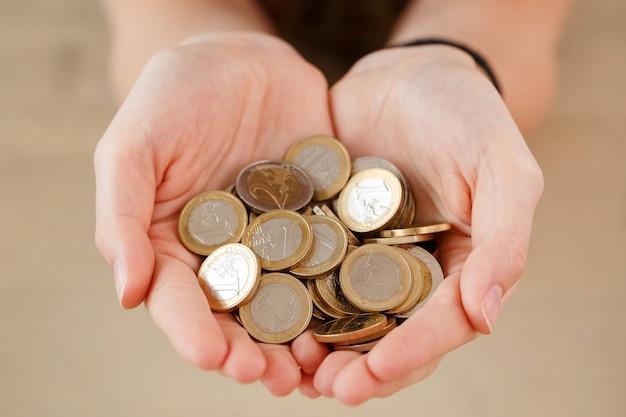 お金、金融。コインの山を持つ女性