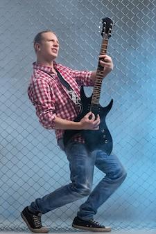 音楽。フェンスの壁にギターを持つ若い音楽家