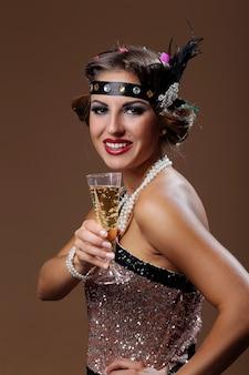 茶色の背景を持つ自分のグラスワインのパーティー女性手