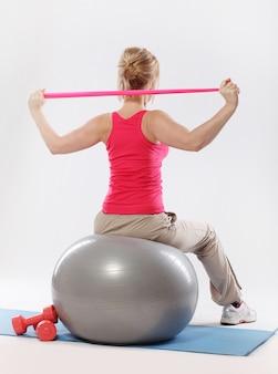 フィットネス安定性ボールでストレッチ体操を行うスポーティな女性