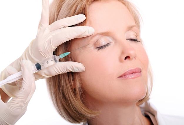 顔の注射を持つ大人の女性