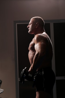Красивый мускулистый мужчина работает и позирует в тренажерном зале