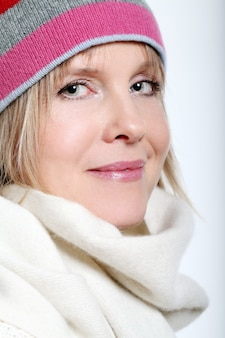 白い背景の上の冬の服を着て熱いお茶と中年女性