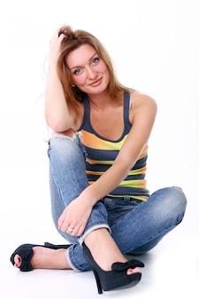 白い背景に対して笑っているかわいい若い女の子のクローズアップの肖像画