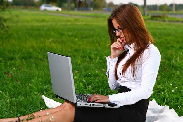 Красивая молодая женщина учится в парке