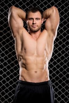 Мощный парень, показывая его мышцы на заборе
